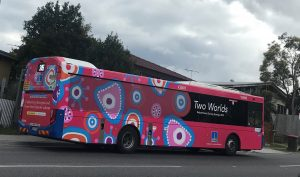 Bright pink bus wrapped with Two Worlds artwork