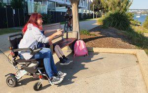 Elisha Matthews in her wheelchair next to a child enjoying time outdoors during Queensland Walks Month