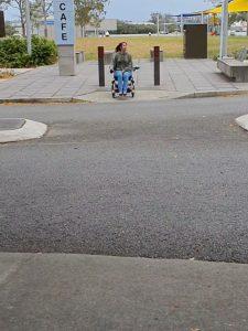 Elisha Matthews approaching kerb ramp to cross the road